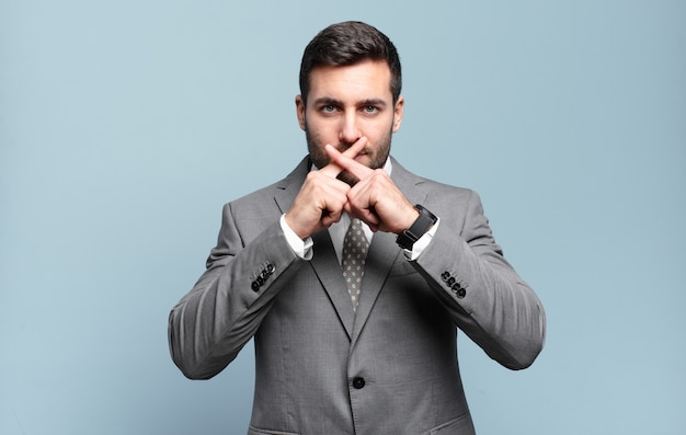 Jonge volwassen knappe zakenman die serieus en ontevreden kijkt met beide vingers vooraan gekruist in afwijzing, vragend om stilte