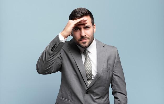 Jonge volwassen knappe zakenman die verbijsterd en verbaasd kijkt, met hand over voorhoofd ver weg kijkend, kijkend of zoekend