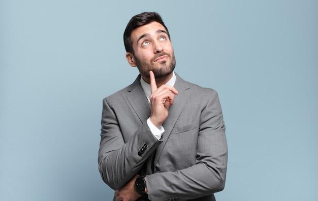 Jonge volwassen knappe zakenman die vrolijk lacht en dagdroomt of twijfelt, opzij kijkend