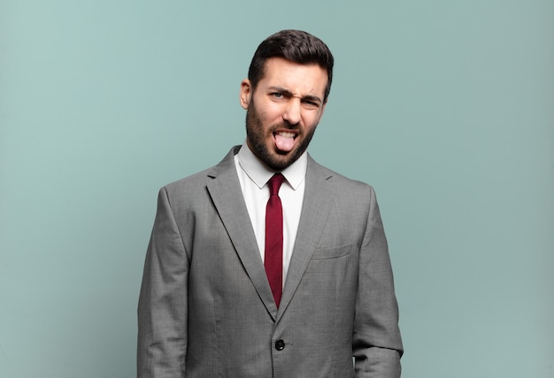 Jonge volwassen knappe zakenman die walgt en geïrriteerd voelt, tong uitsteekt, een hekel heeft aan iets smerigs en vies Premium Foto