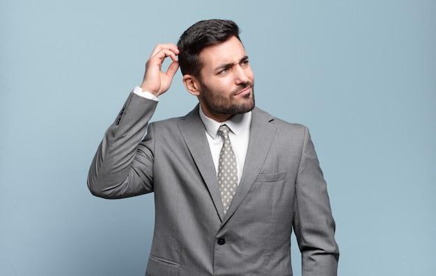 Jonge volwassen knappe zakenman die zich verbaasd en verward voelt, zijn hoofd krabt en naar de zijkant kijkt