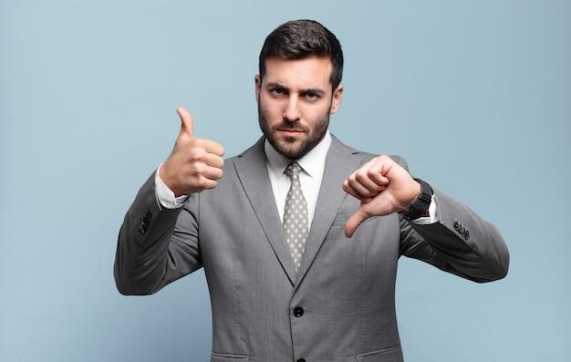 Jonge volwassen knappe zakenman die zich verward, geen idee en onzeker voelt, het goede en het slechte afwegend in verschillende opties of keuzes
