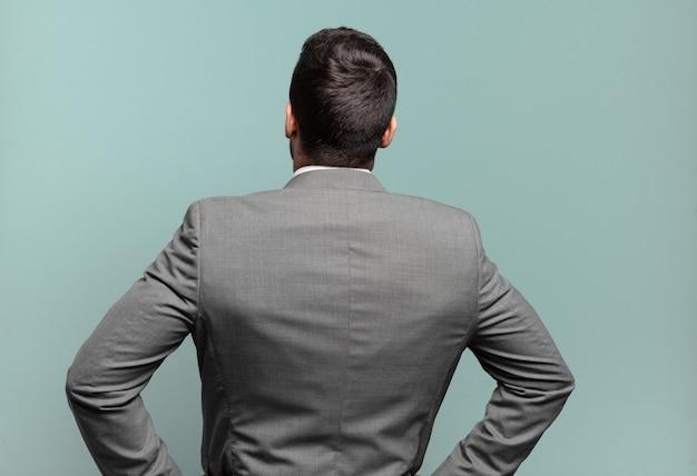 Jonge volwassen knappe zakenman die zich verward of vol voelt of twijfels en vragen, zich afvragend, met handen op de heupen, achteraanzicht