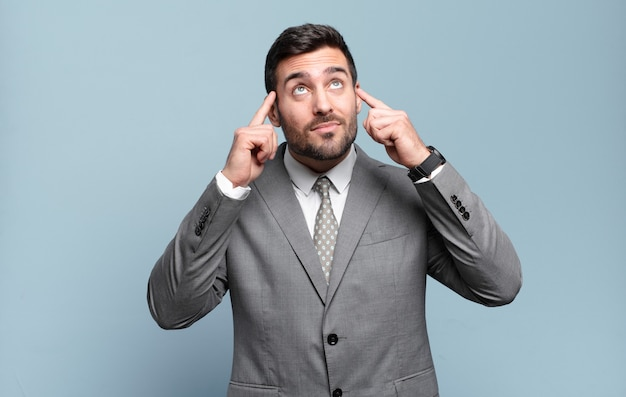 Jonge volwassen knappe zakenman die zich verward voelt of twijfelt, zich concentreert op een idee, hard nadenkt, ruimte aan de zijkant wil kopiëren