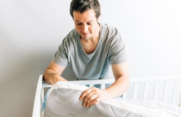Jonge volwassen man die de matras en lakens voorbereidt voor de wieg van zijn zoon. concept van de komst van een baby. vaderschap