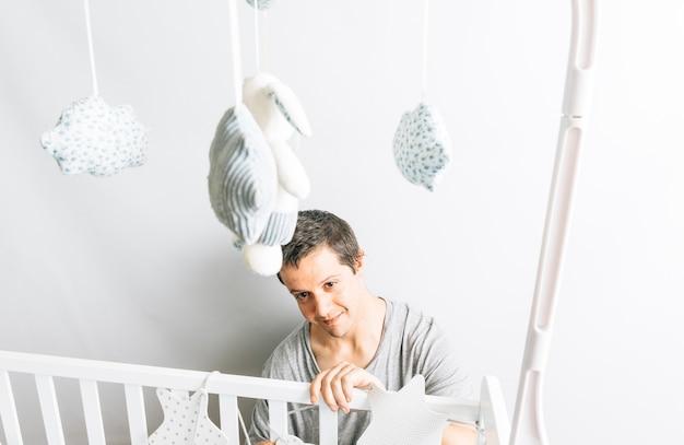 Jonge volwassen man die de wieg voorbereidt en decoreert voor de komst van een baby. nieuw zoonconcept. ouderschap en voorbereidingen