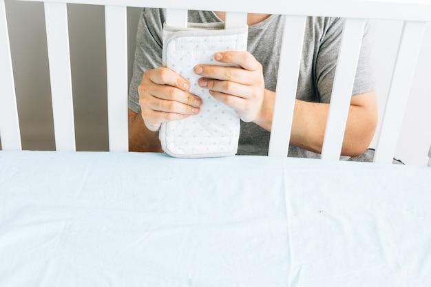 Jonge volwassen man die spatborden in de wieg installeert voor de komst van een baby. concept verwacht een nieuw kind. ouderschap en voorbereidingen