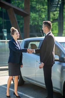 Jonge volwassen man en vrouw in pakken die zich dichtbij auto bevinden