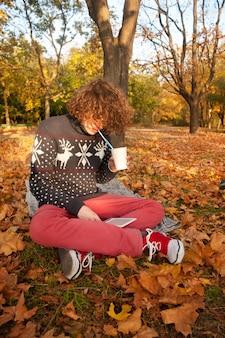 Jonge volwassen man gekleed in gebreide trui met herten, gebreide schoenen en rode spijkerbroek, hebben een vrije tijd zitten in het herfstpark en het elektronische boek lezen.