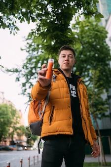 Jonge volwassen man in een gele jas en spijkerbroek loopt op een straat in de stad