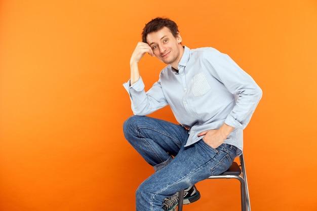 Jonge volwassen man zit op een stoel en raakt het hoofd aan, kijkend naar de camera en een brede glimlach