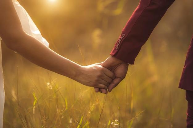 Jonge volwassen mannelijke bruidegom en vrouwelijke bruidholdingshanden bij zonsondergang.