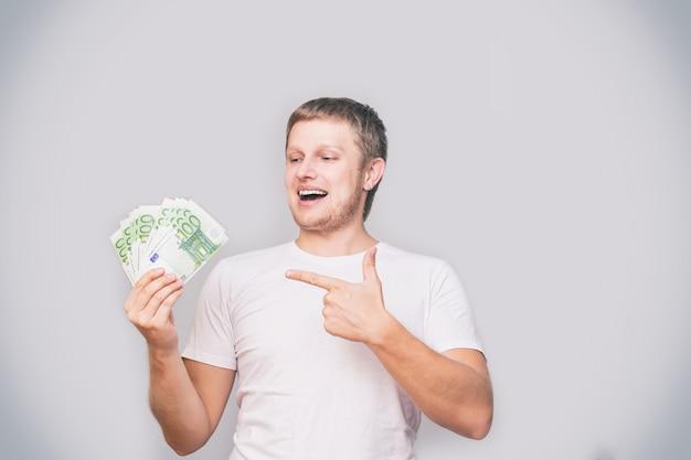 Jonge volwassen mannelijke europeaan ziet er fan van euro geld in wit t-shirt op geïsoleerde achtergrond in studio
