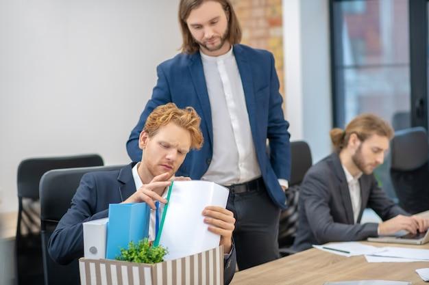 Jonge volwassen mannen in formele pakken bezig in kantoor aan tafel met documenten werken
