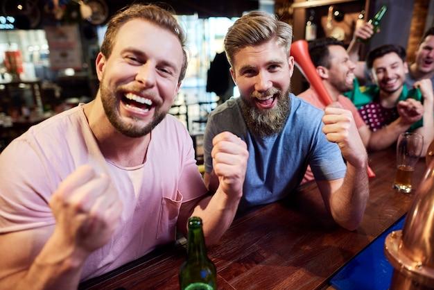 Jonge volwassen mannen vrienden juichen op voetbalteam