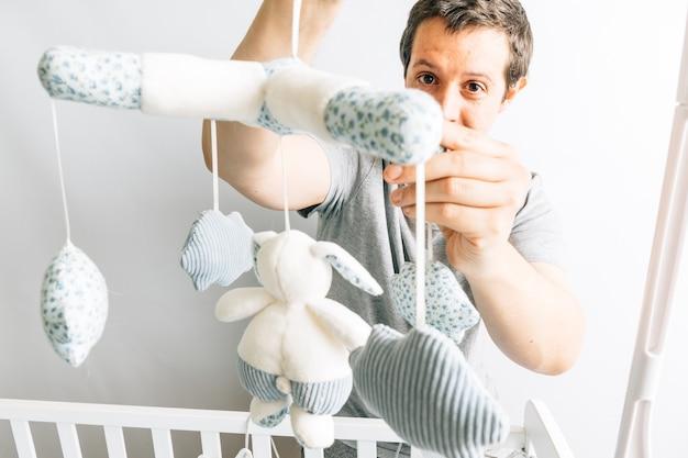 Jonge volwassen mens die speelgoed in de wieg van de baby zet. concept het huis voorbereiden op de komst van een baby. vaderschap