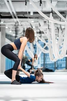 Jonge volwassen moeder die haar dochter helpt om de oefening te doen