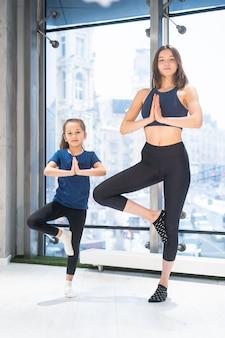 Jonge volwassen moeder en dochtertje samen beoefenen van yoga