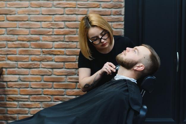 Jonge volwassen mooie blanke vrouw kapper snijdt baard knappe man bij moderne kapperszaak