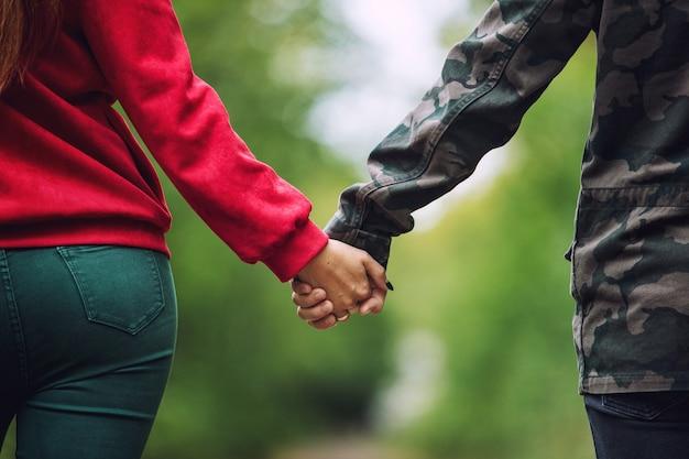 Jonge volwassen mooie verliefde paar wandelen samen in de natuur in het park en hand in hand