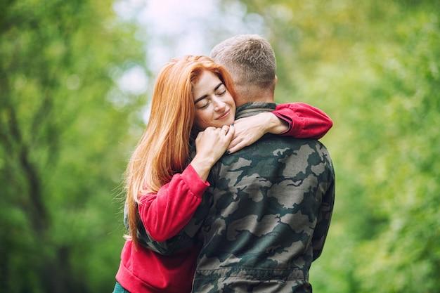 Jonge volwassen mooie verliefde paar wandelen samen in de natuur in het park