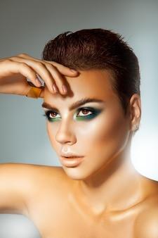 Jonge volwassen mooie vrouw met groene kleurenmake-up en kort kapsel