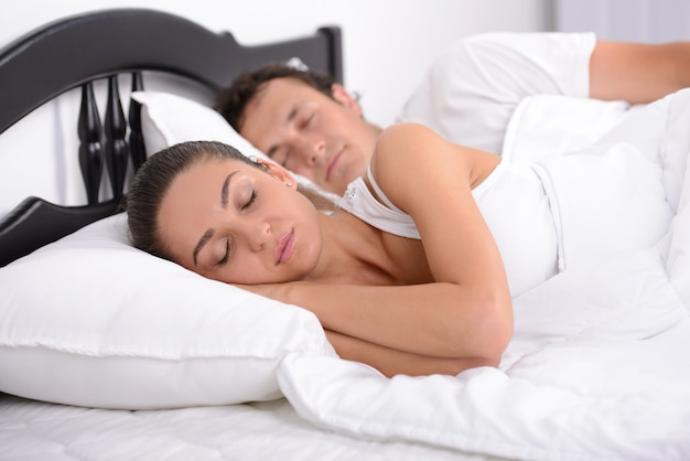 Jonge volwassen paarslaap op het bed in slaapkamer.