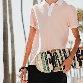 Jonge volwassen schaatser met een skateboard in venice beach, los angeles