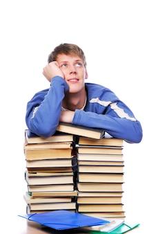 Jonge volwassen student die op hoop van de boeken wordt bijgehouden die omhoog kijkt en denkt.