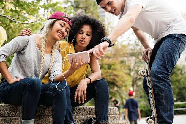 Jonge volwassen vrienden die een smartphone gebruiken en aan muziek in openlucht luisteren