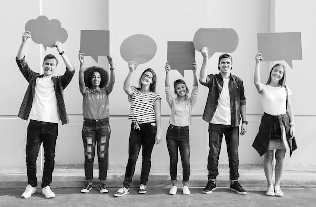 Jonge volwassen vrienden die tekstballonnen met tekstballonnen omhoog houden
