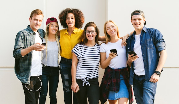 Jonge volwassen vrienden met behulp van smartphones samen buitenshuis jeugdcultuur concept