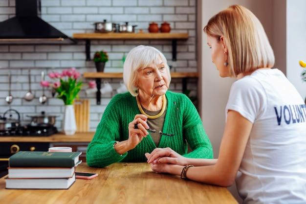 Jonge volwassen vrijwilliger in gesprek met een ouder wordende vrouw in de keuken