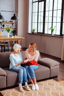 Jonge volwassen vrijwilliger in gesprek met een ouder wordende vrouw op de bank