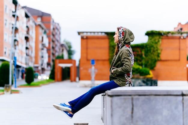 Jonge volwassen vrouw die geniet van een bewolkte dag op straat in de stad die in profiel zit