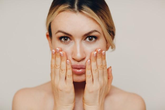 Jonge volwassen vrouw die gezichtsgymnastiek doet, zelfmassage en verjongende oefeningen en gezichtsopbouw voor het optillen van huid en spieren