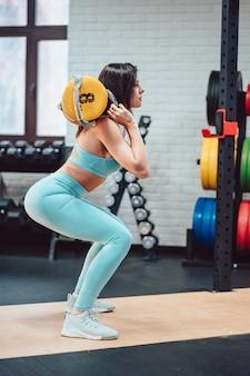 Jonge volwassen vrouw die krachtoefeningen in de gymnastiek doet