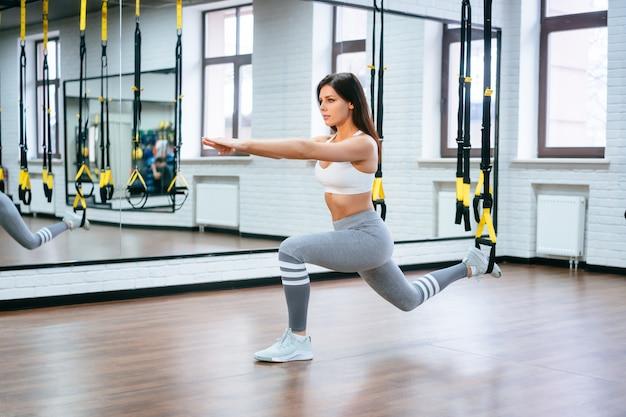 Jonge volwassen vrouw die oefeningen in de gymnastiek doet