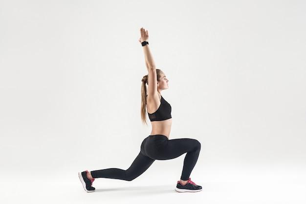 Jonge volwassen vrouw die pilates doet. profiel, zijaanzicht. studio opname, grijze achtergrond