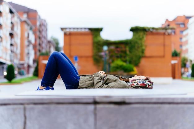 Jonge volwassen vrouw die van een bewolkte dag op straat in de stad geniet die peinzend ligt