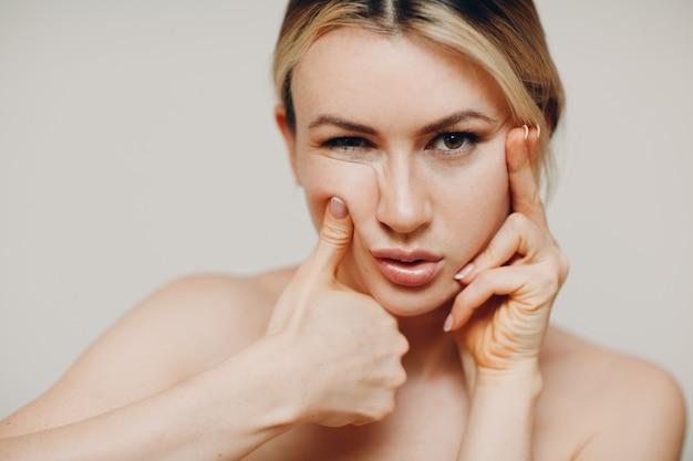 Jonge volwassen vrouw die zelfmassage van de gezichtsgymnastiek en verjongende oefeningen doet gezicht gebouw voor het opheffen van huid en spieren
