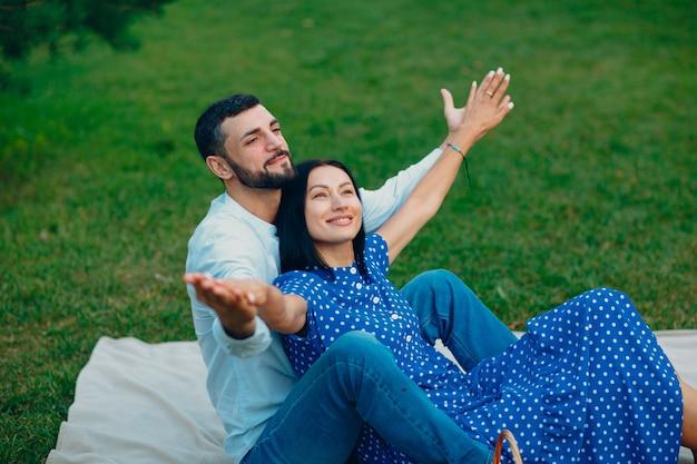 Jonge volwassen vrouw en man paar picknick op groen gras weide in park met open armen