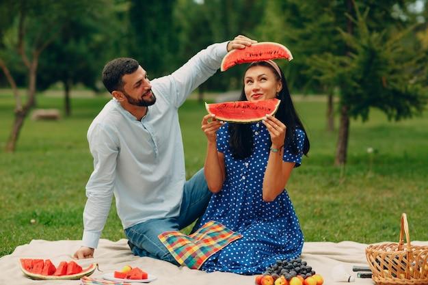 Jonge volwassen vrouw en man paar picknick op groen gras weide in park met plezier met watermeloen