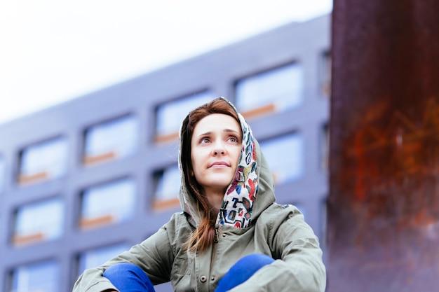 Jonge volwassen vrouw genieten van een bewolkte dag op straat in de stad