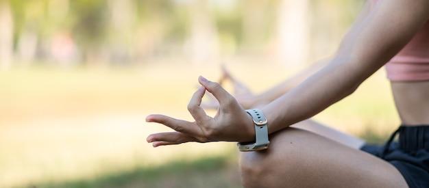 Jonge volwassen vrouw in sportkleding doet yoga in het park buiten.