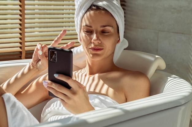 Jonge volwassen vrouw ligt in de badkamer selfie te nemen