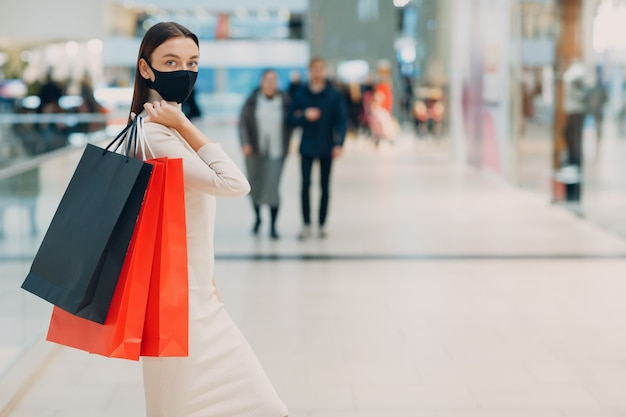 Jonge volwassen vrouw met beschermend medisch gezichtsmasker met papieren boodschappentassen in handen bij winkelcentrum