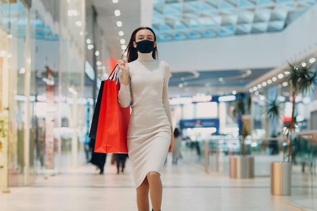 Jonge volwassen vrouw met beschermend medisch gezichtsmasker met papieren boodschappentassen in handen in de winkel