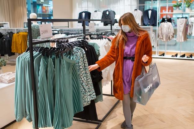 Jonge volwassen vrouw met beschermend medisch gezichtsmasker met papieren boodschappentassen in handen in het winkelcentrum