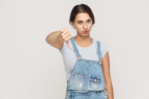 Jonge volwassen vrouw met duim omlaag geïsoleerd op een grijze achtergrond. studio opname.